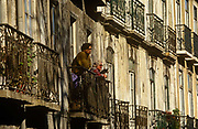 Locals look at street life below from the crumbling balconies of their old apartment block in Lisbon's Biarro Alto district. The woman holds her pet dog and a younger man leans on his arms, supported by rickety railings in afternoon sunshine. Bairro Alto is one of the oldest districts in Lisbon. Dozens of fado singing clubs animate the area. All major Portuguese newspapers once had their offices in here. Prostitution was visible and considerable. Since the 1990s, Bairro Alto went through major changes. Lisbon's city council made extensive repairs, and dozens of new restaurants, clubs and trendy shops were opened. Many young people moved into the area. Cars were banned (except for residents and emergency vehicles).