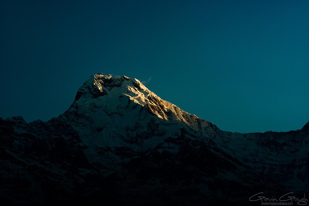 A Himalayan mountain peak illuminated by the first light of the day at sunrise, Tadapani Guest House, Tadapani, Nepal
