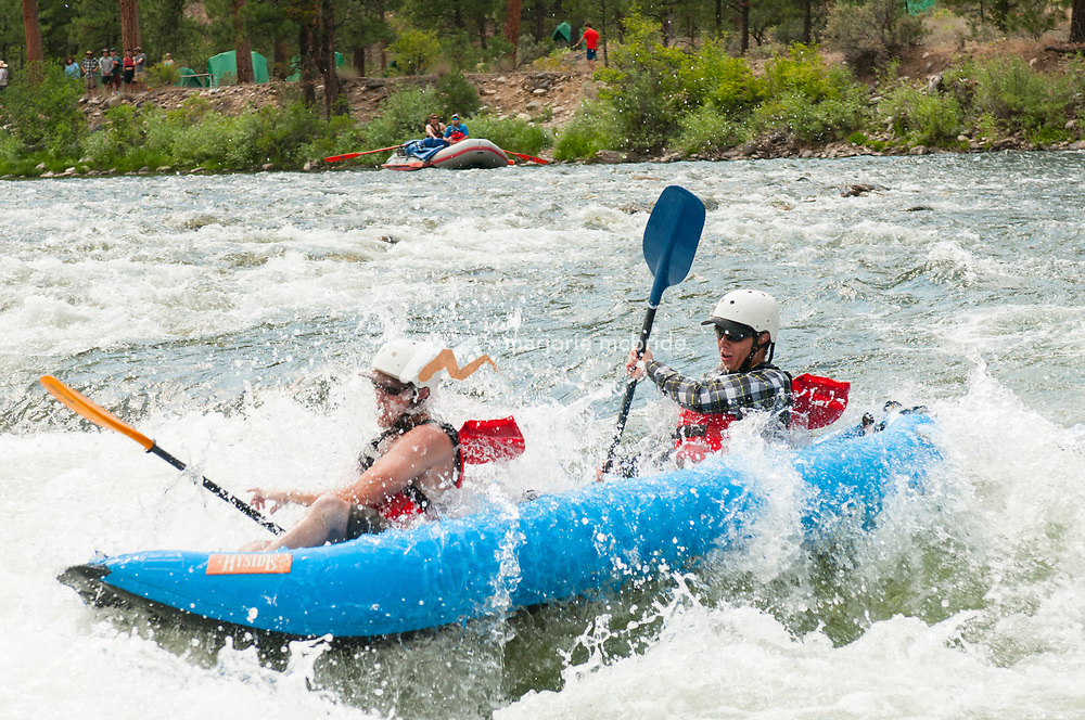 Brothers tandem kayaking Marble Creek rapid on the Middle Fork of the Salmon River, Idaho.