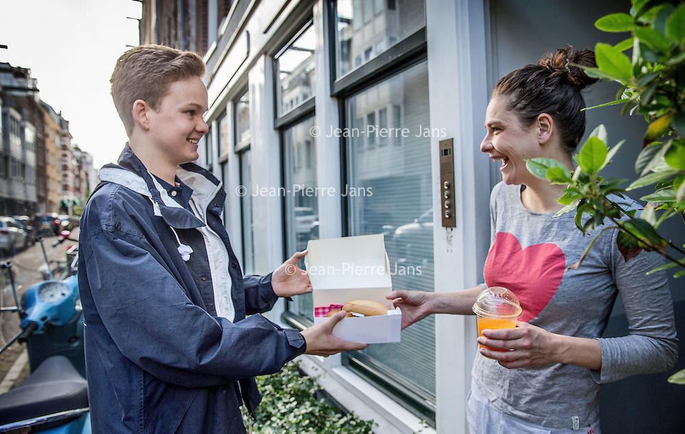 Nederland, Amsterdam, 3 juli 2016.<br /> De Croissant Boys, een familiebedrijf bestaande uit 3 broers die zondagochtend tussen 9-12 uur verse croissants met roomboter en/of jam en verse jus d'orange bij u thuis bezorgt.<br /> Op de foto: Willem rosier levert de croissant met jus af bij een klant.<br /> <br /> The Croissant Boys, a family business consisting of three brothers who deliver fresh croissants with butter and / or jam and fresh orange juice to your home on sunday mornings between 9-12 am.  <br /> <br /> Foto: Jean-Pierre Jans