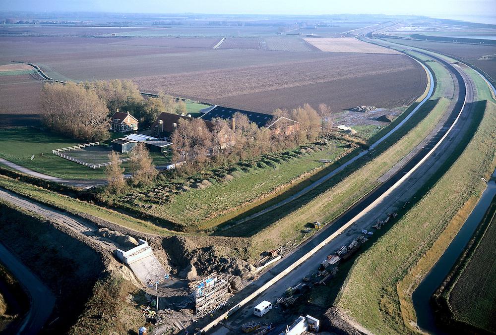 Nederland, Zeeland, Zuid-Beveland, Korte Zuidweg, 15/11/2001; trace toegangsweg Westerscheldetunnel, Westerschelde ad horizon;  de dijk aan weerszijden van de weg, vormt geluidswal en zorgt voor  inpassing in het omliggende polderlandschap; lokale weg krijgt viaduct over de toegangsweg.<br /> luchtfoto (toeslag), aerial photo (additional fee)<br /> photo/foto Siebe Swart