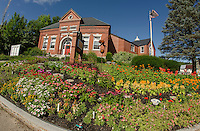 Beautiful flower gardens with #7 Dragonfly of the Meredith Sculpture Walk adorn the front lawn of the Meredith Public Library.  (Karen Bobotas/for the Laconia Daily Sun)