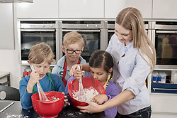 Teacher with students beating cream in mixing bowl with wire whisk in home economics class, Bavaria, Germany