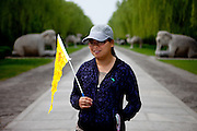 Tourist guide with a yellow flag at The Ming Dynasty Tombs in Nanjing which are located about 50 kilometers due north of central Beijing, within the suburban Changping District of Beijing municipality. Beijing is the capital of the People's Republic of China and one of the most populous cities in the world with a population of 19,612,368 as of 2010.
