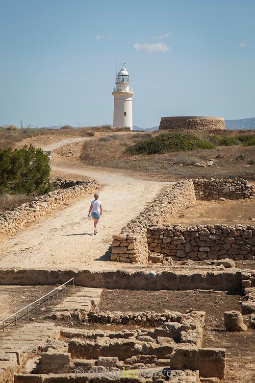 A woman walking towards a Paphos lighthouse, Paphos, Cyprus.