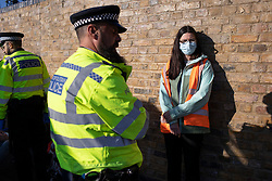 © Licensed to London News Pictures. 03/10/2021. London, UK. An arrested activist from Insulate Britain at the entrance to the Blackwall tunnel after the group blocked the tunnel earlier this morning. Insulate Britain have successfully blocked various roads around the capital over a number of weeks, resulting in a court injunction banning them from going near the M25 motorway.  Photo credit: George Cracknell Wright/LNP