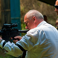 Csaba Hende Defense Minister for Hungary presents his shooting skills with a US made M4 rifle during the presentation of the coalition support for Hungary by the US military in Szolnok, Hungary on July 18, 2011. ATTILA VOLGYI