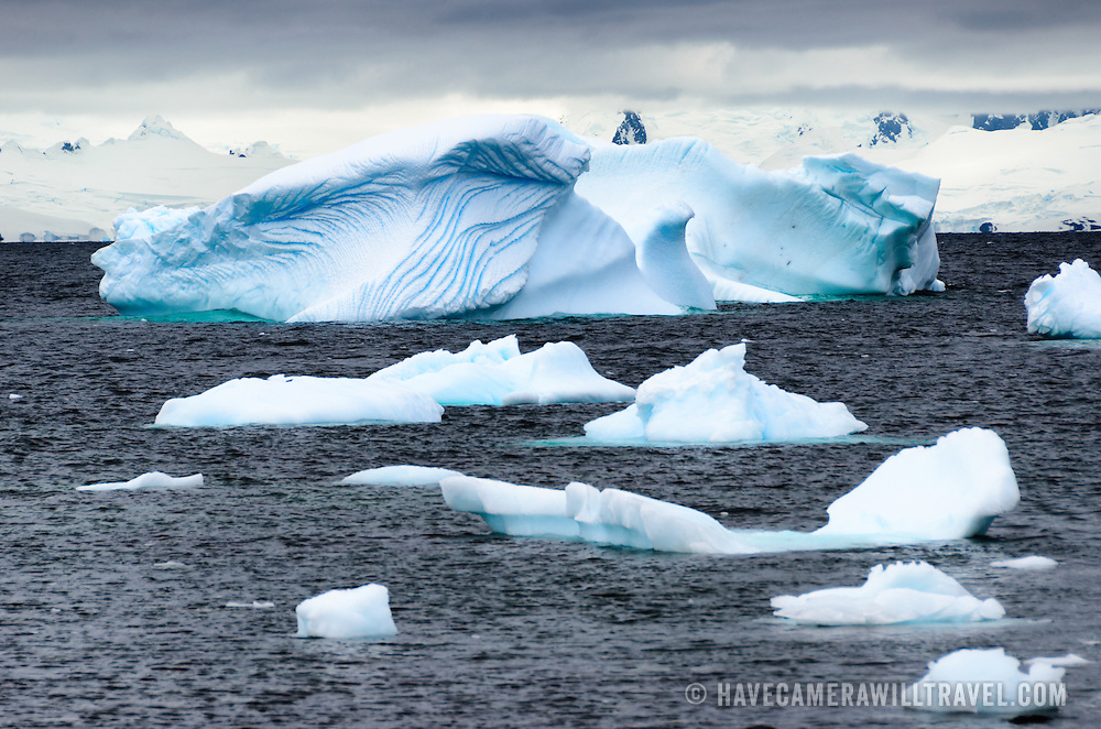 A series of small and medium-sized bue icebergs float in the waters near Two Hummock Island on the western side of the Antarctica Peninsula.