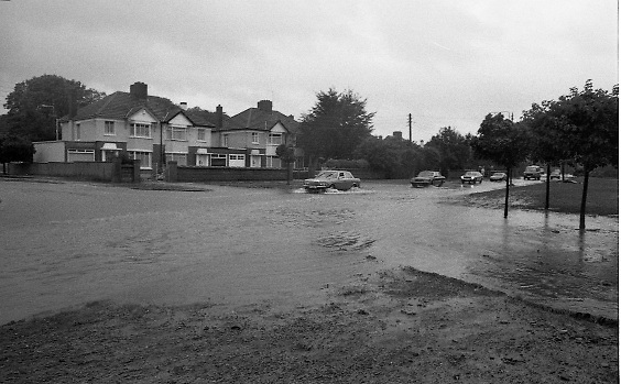 """Flooding at the Dodder..1986..26.08.1986..08.26.1986..28th August 1986..As a result of Hurricane Charly (Charlie) heavy overnight rainfall was the cause of severe flooding in the Donnybrook/Ballsbridge areas of Dublin. In a period of just 12 hours it was stated that 8 inches of rain had fallen. The Dodder,long regarded as a """"Flashy"""" river, burst its banks and caused great hardship to families in the 300 or so homes which were flooded. Council workers and the Fire Brigades did their best to try and alleviate some of the problems by removing debris and pumping out some of the homes affected..Note: """"Flashy"""" is a term given to a river which is prone to flooding as a result of heavy or sustained rainfall...Photograph of motorists trying to avoid the worst of the flooding by driving on the 'wrong' side of the road on the Lr. Dodder Road, Rathfarnham.. Motorists were advised to be vigilant as manhole covers had been displaced by the water pressure and were lying unseen underwater."""