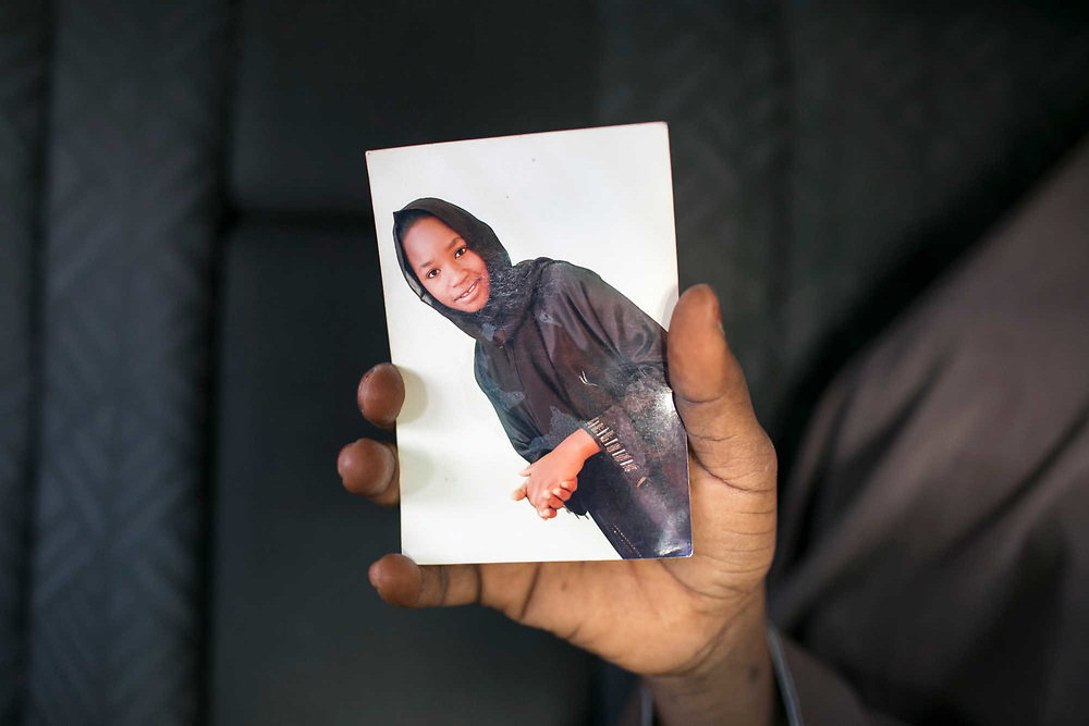 Kaltum, an older sister of Zainab, 24, holds Zainab's only remaining picture outside her relatives' house in Maiduguri, Nigeria, April 30, 2019. Kaltum said Zainab was abducted by Boko Haram four years ago in 2015, and stayed in the forest for nine months. After being discovered by a passerby on the streets of Mubi Local Government, the family discovered that she lost her consciousness and suffered from mental disorder. Zainab never told anyone about what had happened. The family admitted her to the psychiatric center in Maiduguri, but her symptoms did not improve. On a February afternoon, she vanished from the relatives' house and has been missing since then.