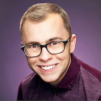 Joe Tracini smiles mischievously at the camera, Actor headshot shot against purple background to compliment Joe's purple top