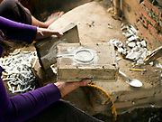 Ms Vanthone, a metalworker opens a wooden mould used to make bracelets from recycled aluminium sourced from Vietnam War debris and melted in an earthen kiln in Ban Naphia, a remote Tai Phouan village in mountainous Xieng Khouang Province in Northern Laos. Laos is the most bombed country, per capita, in the world with more than two million tons of ordnance dropped on it during the Vietnam War from 1963 to 1974.12 artisan families began transforming war scrap into spoons (150,000 per year) in the 1970s to supplement subsistence farming activities. Supported by the Swiss NGO Helvetas, the project works to make the scrap metal supply chain safer for artisans and scrap collectors by collaborating with organisations such as Mines Advisory Group (MAG) that specialise in unexploded ordnance removal and education. More recently the villagers have started making bracelets and other items.