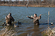 Gary Friend uses a long pole to retrieve decoys while duck hunting in Shamrock, Oklahoma