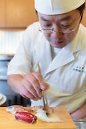 Sushi chef Masatoshi Yoshino is applying the nikiri shoyu (special soy sauce for sushi) on a squid nigiri sushi at his restaurant Yoshino Sushi Honten, Tokyo, Japan