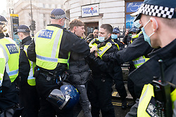 © Licensed to London News Pictures. 19/12/2020. London, UK. Police officers arrest a protester for taking part in an Anti Covid-19 lockdown demonstration in Central London. The group against the current tier regulations and against vaccination for the Covid-19 disease. Photo credit: Ray Tang/LNP