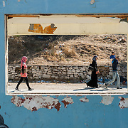 A group of people walking in Moria camp through the window of the abandoned camp refectory.
