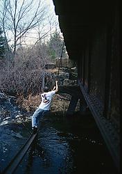 Kid Swinging On Railroad Trestle