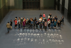 "© Licensed to London News Pictures. 01/10/2018. LONDON, UK. Volunteers pose after leaving body impressions on the heat-sensitive floor. Unveiling of the this year's Hyundai Commission by Cuban artist and activist Tania Bruguera at Tate Modern.  The work is called ""an ever-increasing figure"", which represents the scale of mass migration and the risks involved.  Visitors are invited to interact with the work which comprises a heat-sensitive floor, which includes a portrait of a person's face beneath, combined with low frequency sounds.  The work is on display 2 October to 24 February 2019..  Photo credit: Stephen Chung/LNP"