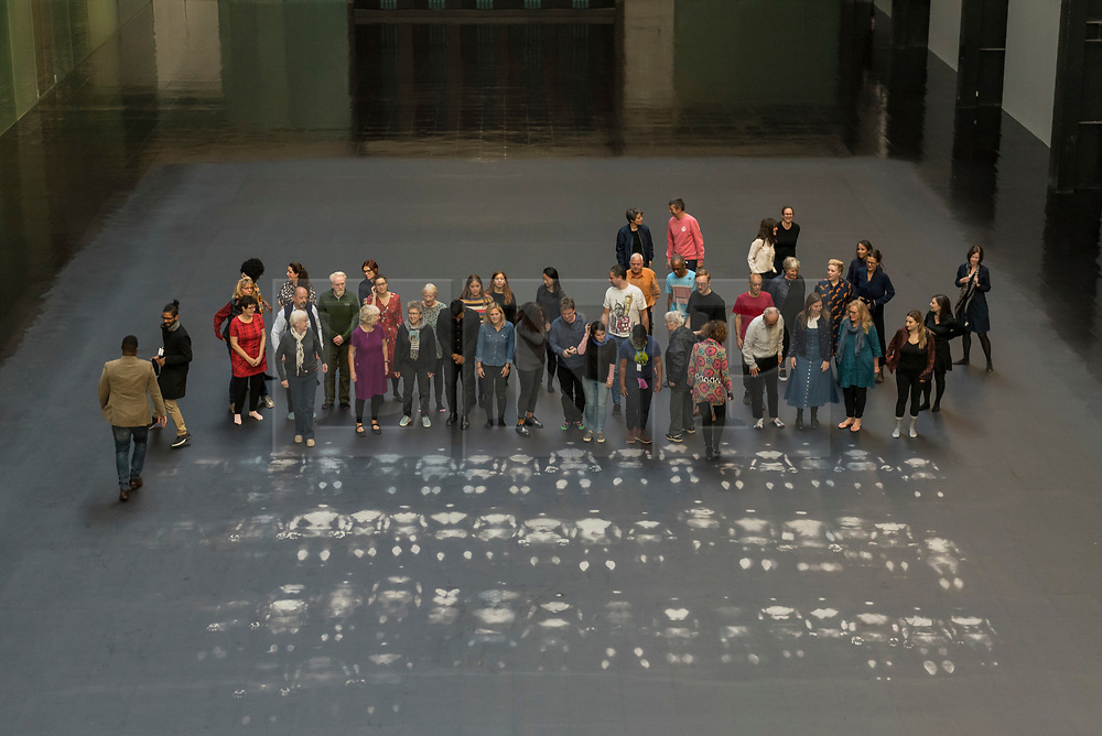 """© Licensed to London News Pictures. 01/10/2018. LONDON, UK. Volunteers pose after leaving body impressions on the heat-sensitive floor. Unveiling of the this year's Hyundai Commission by Cuban artist and activist Tania Bruguera at Tate Modern.  The work is called """"an ever-increasing figure"""", which represents the scale of mass migration and the risks involved.  Visitors are invited to interact with the work which comprises a heat-sensitive floor, which includes a portrait of a person's face beneath, combined with low frequency sounds.  The work is on display 2 October to 24 February 2019..  Photo credit: Stephen Chung/LNP"""