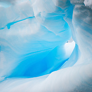 A smooth, small cave that is blue in the light in an iceberg in Curtis Bay on the Antarctic Peninsula.