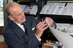 The Duke of Edinburgh, tests his pen prior to signing a portrait of himself, during his official visit to the St Michael's Care Complex in Aylsham, Norfolk, which provides care for the elderly.