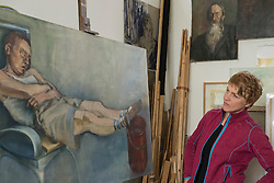 Female artist looking at painting on easel, Bavaria, Germany