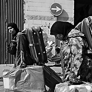 CEUTA, SPAIN - JUNE 27, 2010 : Moroccan women carrying goods at the warehouses next to the pedestrian cross border of  Biutz. Thousands  of people are involved in transporting smuggled goods from Ceuta (an Spanish enclave on the North African coast) to Morocco, it is estimated that every day enter 10.000 porters, mostly women, that it make between three and five trips to Morocco with all types of products purchased on  the warehouse border area of  Biutz in Ceuta, Spain.( Photo by Jordi Cami )