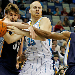 January 18, 2012; New Orleans, LA, USA; New Orleans Hornets center Chris Kaman (35) is defended by Memphis Grizzlies center Marc Gasol (33) and point guard Mike Conley (11) during the first half of a game at the New Orleans Arena.   Mandatory Credit: Derick E. Hingle-US PRESSWIRE