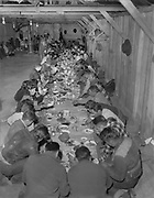 """Y-480418-24. Celilo Village longhouse, Feast of the First Salmon dinner. April 18, 1948. The purpose of this annual feast was to give thanks and welcome the first salmon to start the spring run up the Columbia River. With the beginning of each year's new salmon run, Celilo Indians could eat fresh fish instead of the dried salmon they preserved from the year before. Historically this was expected to be the second or third week of April, but the Indians would begin the celebration only after the fish actually appeared. Just the year before, in 1948, Chief Tommy Thompson had gone to the Warm Springs to invite all the Indians to Celilo for the feast on the weekend the fish were anticapated, but when the fish didn't run he had to postpone the ceremony for another week. And nine years before, in 1940, the feast was held on the first weekend of April, at the time it was said to be the earliest the feast had ever been held. Attendance had ranged from, according to newspaper reports, 47 Indians in 1938, rising to 600 at this one. The following year, in 1949, the feast was again postponed due to no fish. With the end of Celilo in the forseeable future, crowds continued to grow and finally, in 1956, at the last Feast of the First Salmon before the innundation, unseasonably warm weather in the late winter thawed the ice fields and Celilo falls flooded making fishing impossible. Celilo Indians were forced to buy 400 pounds of salmon on the commercial market in Portland to feed the crowd, which the newspaper reported as being comprised of """"More white folks with cameras than Indian fishermen with dipnets."""" Ever since the falls were covered, the feast has been held at a pre-arranged time."""