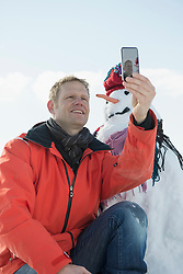 Man taking picture with smart phone of him and snowman, Bavaria, Germany