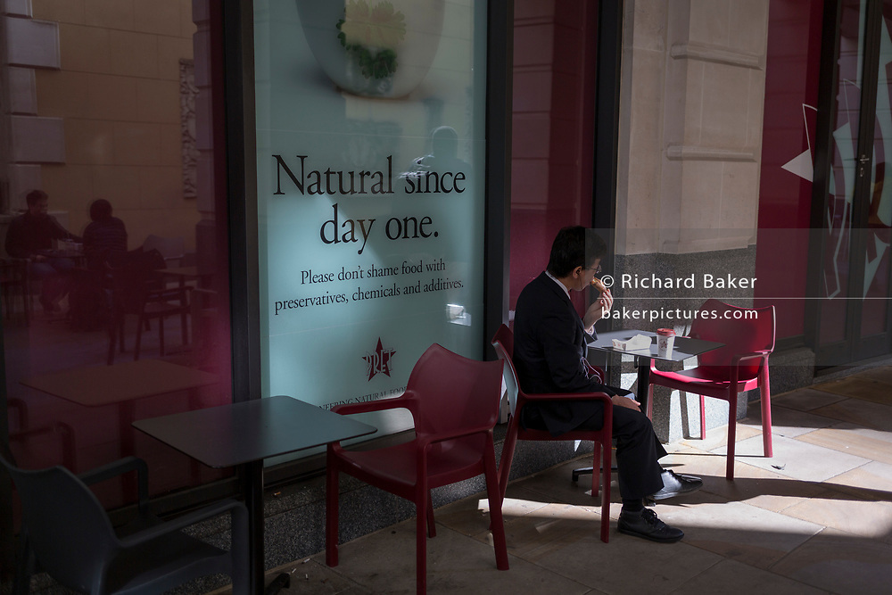 A lone businessman eats a snack outside the Lombard Street branch of Pret a Manger, on 10th May 2017, in the City of London, England.