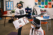 17 FEBRUARY 2021 - DES MOINES, IOWA: A student wearing a mask and social distancing talks to her fourth grade classmates at Walnut Street School in downtown Des Moines about her father's work as an artist. Des Moines Public Schools (DMPS) opened to in person education this week after teaching most of the 2020-2021 school year either remotely or with a hybrid/remote learning model. Elementary school classrooms, which used to sit 2-4 students at a table, have gone to individual desks, placed 6 feet apart, in classrooms. Students are required to wear masks for most class activities. The district has ended its hybrid model. The Governor of Iowa has aggressively pushed schools to return to in person education, going so far as to threaten to withhold funds from districts that don't return to in person classes. DMPS, the largest school district in Iowa, has resisted the Governor's push because Polk County, IA, has been a Coronavirus/COVID-19 hotspot with positivity rates well above 10 percent. The district was recently able to vaccinate many teachers and positivity rates have fallen to 9 percent, making it safer to reopen schools.     PHOTO BY JACK KURTZ