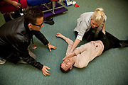 Intense medical session with a tutor / instructor pretending to be suffering from a head injury for trainees in their first weeks. Virgin Atlantic air stewardess and steward training at The Base training facility in Crawley. Potential hostesses are put through a gruelling 6 week training program, during which they are tested to their limits. With exams every day requiring an 88% score to pass. The Base is a modern environment for a state of the art airline training situated next to Virgin Atlantic's HQ.