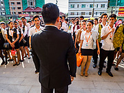 """13 FEBRUARY 2019 - SIHANOUKVILLE, CAMBODIA: A supervisor of Cambodian workers at the BWin Casino, a newly opened casino in downtown Sihanoukville, gives a debriefing at the end of their overnight shift at the casino. There are about 80 Chinese casinos and resort hotels open in Sihanoukville and dozens more under construction. The casinos are changing the city, once a sleepy port on Southeast Asia's """"backpacker trail"""" into a booming city. The change is coming with a cost though. Many Cambodian residents of Sihanoukville  have lost their homes to make way for the casinos and the jobs are going to Chinese workers, brought in to build casinos and work in the casinos.      PHOTO BY JACK KURTZ"""