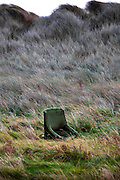 Abandoned chair on Bull Island, Dublin, camouflaged amongst the marram grass. ..Bull Island is a UNESCO protected biosphere reserve in the Northern suburbs of Dublin. It features two golf clubs, and Dollymount beach, used for kitesurfing and other outdoor activities. Wildlife includes seals and bird life.<br /> <br /> <br /> Limited edition Giclée Prints available - contact me for more details.