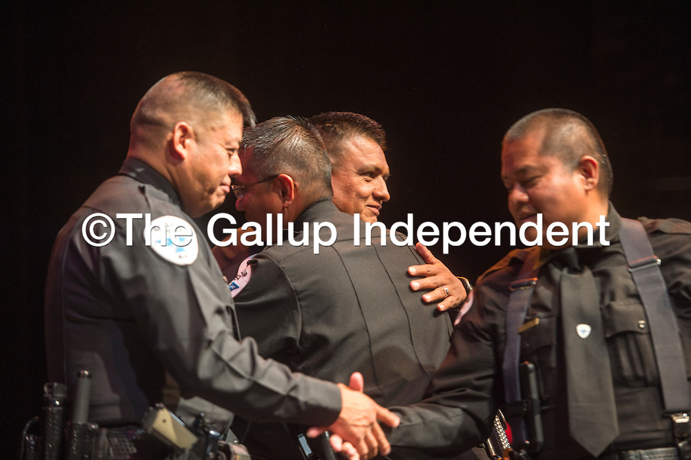 Lieutenant Francie Martinez receives a hug from Chief Franklin Boyd while Sergeant Mark Spencer, left, shakes the hand of Captain Edwin Yazzie after all four men receive promotions at a ceremony held at El Morro Theater in Gallup Friday.