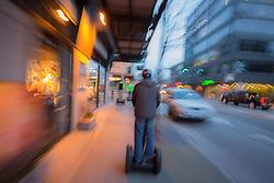 United States, Washington, Seattle, man riding Segway through downtown at dusk (motion)