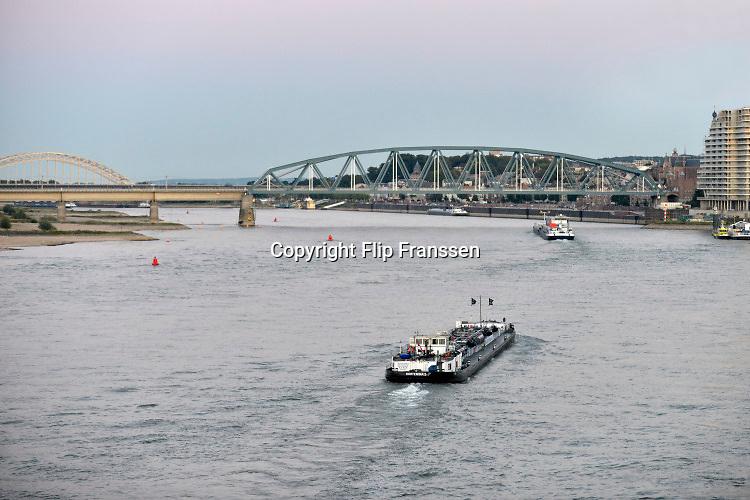 Nederland, Nijmegen, 9-10-2017Een binnenvaartschip passeert  Nijmegen ter hoogte van de spoorbrug .  Binnenvaartschepen . De Waal is het Nederlandse deel van de Rijn en de belangrijkste vaarroute van en naar Rotterdam en Duitsland . Aftakkingen zijn de minder bevaren Nederrijn en IJssel.Foto: Flip Franssen
