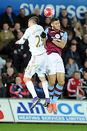 Swansea's Gylfi Sigurdsson (l) and Aston Villa's Rudy Gestede challenge for a header. Barclays Premier league match, Swansea city v Aston Villa at the Liberty Stadium in Swansea, South Wales on Saturday 19th March 2016.<br /> pic by  Carl Robertson, Andrew Orchard sports photography.