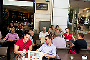 People out having afternoon coffee at cafes in Monastiraki. There is a very popular cafe scene in Athens with all sorts of people hanging out, relaxing and avoiding the hottest part of the day with a chilled coffee or drink. Athens is the capital and largest city of Greece. It dominates the Attica periphery and is one of the world's oldest cities, as its recorded history spans around 3,400 years. Classical Athens was a powerful city-state. A centre for the arts, learning and philosophy.