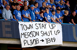 Huddersfield Town fans hold up a banner aimed at Sky Sports pundit Paul Merson after he predicted the team would be would be relegated.