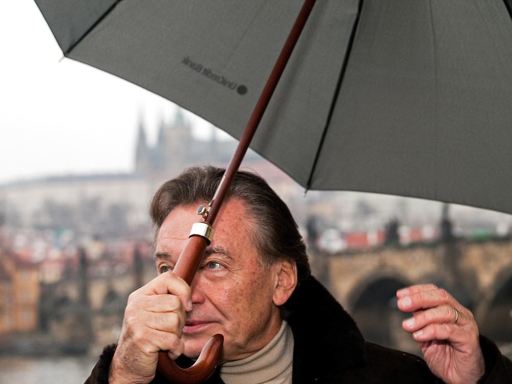 Czech popular singer Karel Gott covering himself with an umbrella against starting snow close to Pragues Charles Bridge.