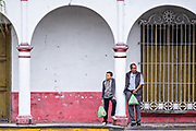 People wait under a colonnade for the rain to stop in Tlacotalpan, Veracruz, Mexico. The tiny town is painted a riot of colors and features well preserved colonial Caribbean architectural style dating from the mid-16th-century.