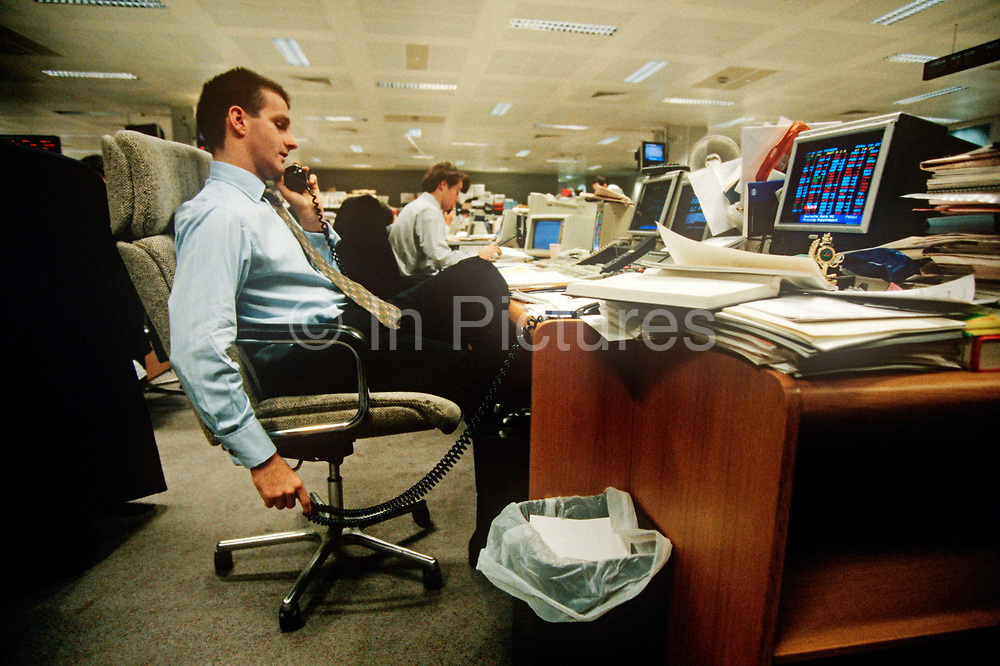 A 1990s banker speaks on the phone and in front of his computer, on the trading floor of credit Lyonnais in the City of London aka The Square Mile, the capitals financial centre, on 20th May 1993, in London, England.