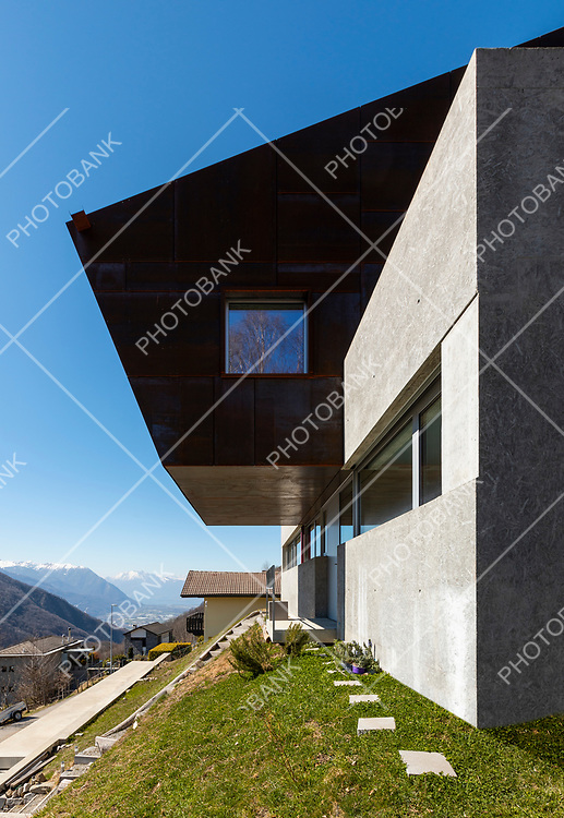 Exterior modern isolated villa with garden, surrounded by nature. Iron and concrete cladding. Nobody inside