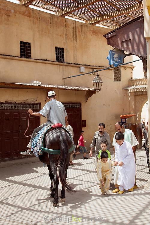 Daily life as people move around the narrow streets of the medina in Fes, Morocco