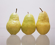 Three pears on a white surface