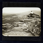 Magic lantern slide of woman sitting on mountain peak in countryside England, UK circa 1900 possibly Dartmoor