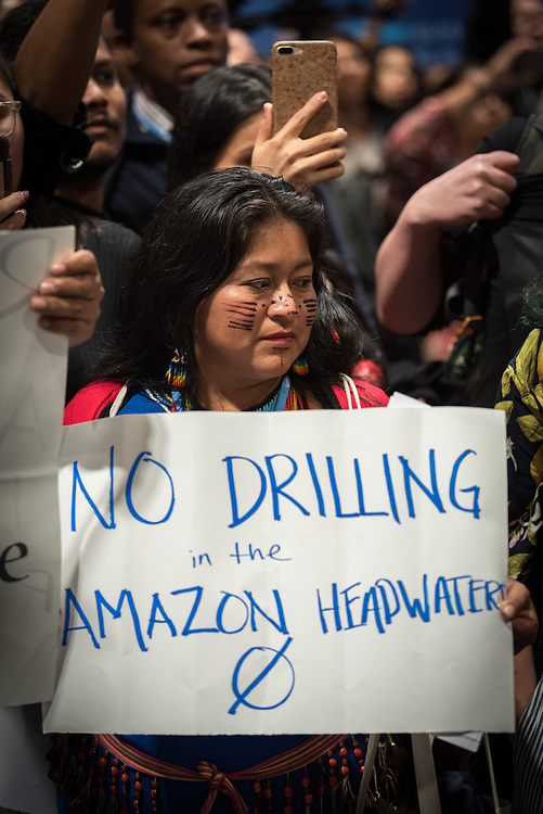 """11 December 2019, Madrid, Spain: An indigenous woman holds a sign reading """"No drilling in the Amazon headwater"""", as hundreds of civil society and other actors hold an unauthorized protest outside the plenary hall of COP25 in Madrid, to draw attention to the failures of the climate talks and to call on rich countries to step up and pay up for real solutions, and to highlight the threat of loopholes, false solutions like carbon markets, and the need for those who caused the climate crisis to pay up for loss and damage while respecting human rights."""