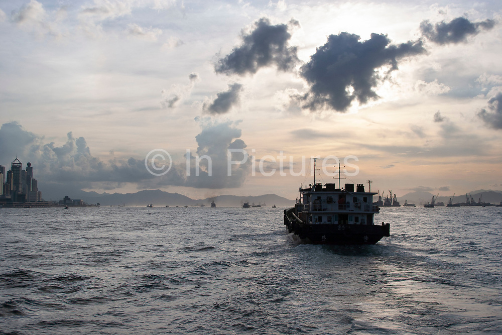 Transportation vessels pass through Hong Kong Harbour, China. This busy shipping lane is host to thousands of container carriers, and other transport ships moving goods throughout Asia. At dawn and dusk these ships cast ghostly figures throughout the shipping lanes around Hong Kong and its surrounding islands.